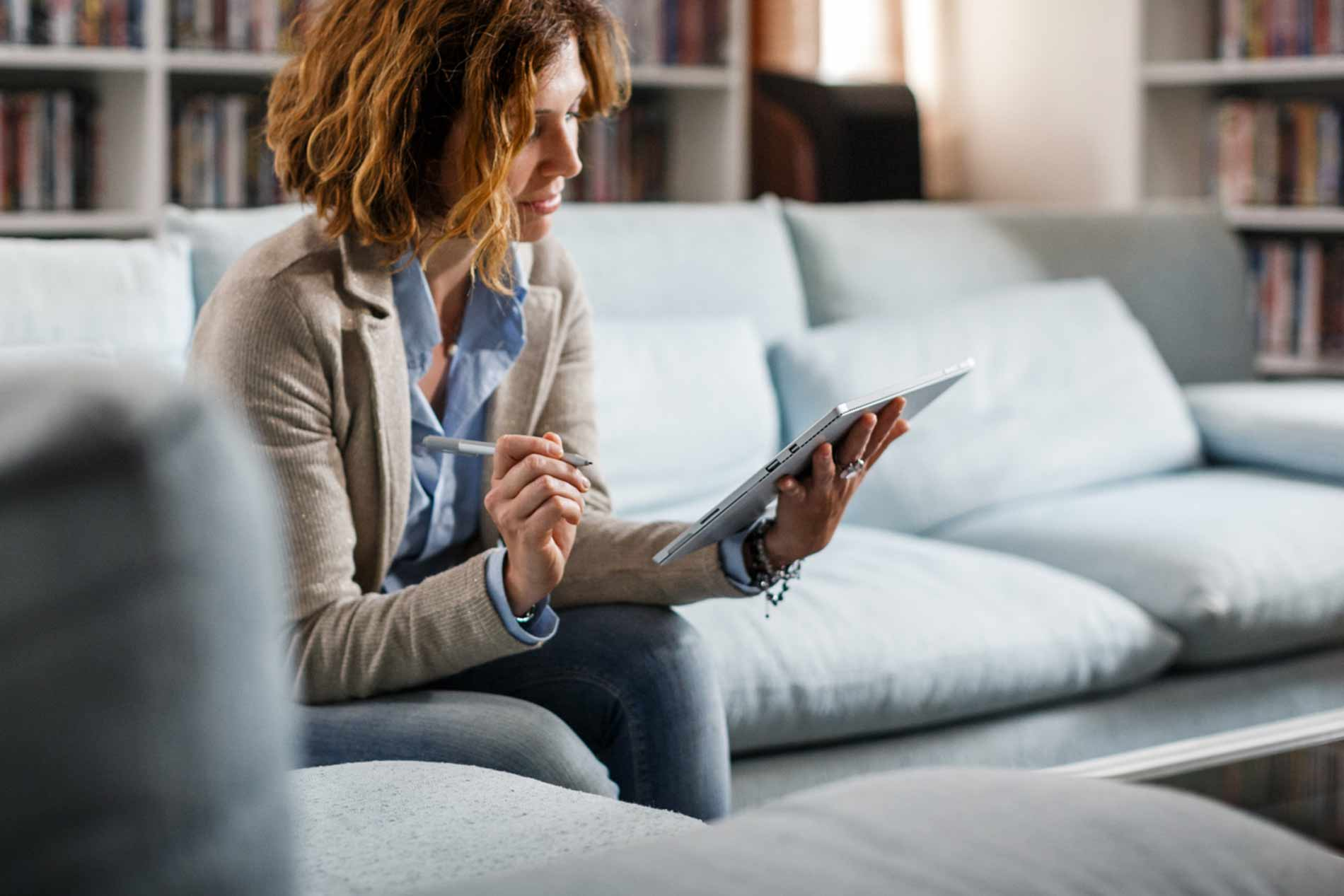background, woman at home, signing a contract on her tablet